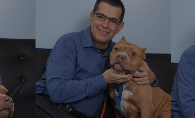 Dr. Joseph Hahn sitting on couch with dog
